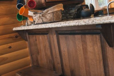 Stained Birch cabinet peninsula paneling with log siding wall