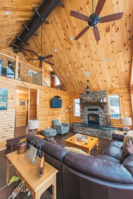 A-frame cottage living room and loft with pine log siding, pine t&g ceiling and stone fireplace