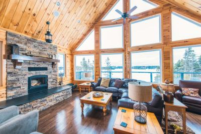 A-frame cottage living room with pine log siding, pine t&g ceiling and stone fireplace