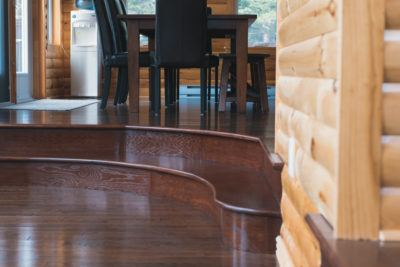 Curved stair treads and bullnose in stained oak stepping into sunken living room