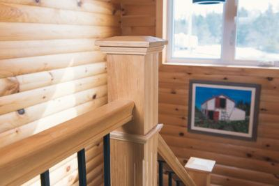 Detail of Solid Pine post top and rail. Pine Log siding on walls.