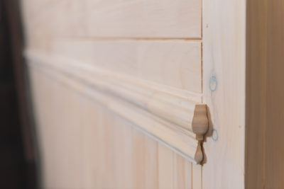 Detail of chair rail on white wash wood paneled wall