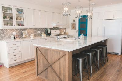 Overall shot of white kitchen cabinets with large stained island and turquoise door