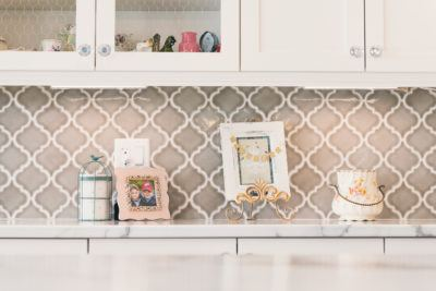 grey tile backsplash shown in white kitchen with crystal and chrome knobs