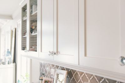 Chicken wire inset in top cabinets of white kitchen with crystal and chrome knobs