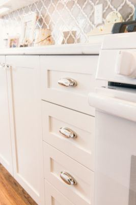 detail of drawers in white kitchen cabinets with chrome cup pulls