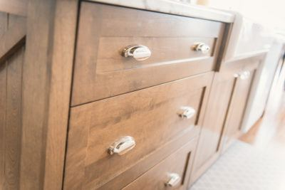 detail of deep drawers in solid birch stained brown with chrome cup pulls