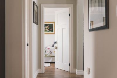 Craftsman Door opened to a guest room showing MDF baseboard and casing