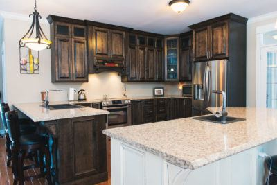 Overview of birch cabinets in a dark stain with antique white island