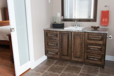 Custom vanity cabinet in stained birch shown with frosted pocket door