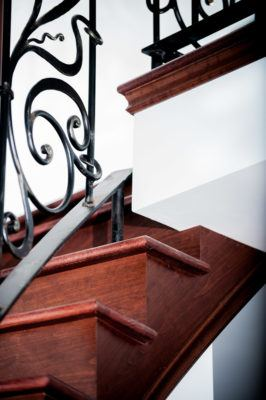 detail of birch stairs stained mahogany with custom wrought iron rails