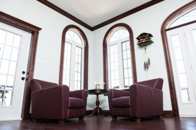 Cherry mouldings stained mahogany around arched windows, doors, ceiling and baseboard