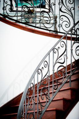 winding birch stairs stained mahogany with custom wrought iron rails