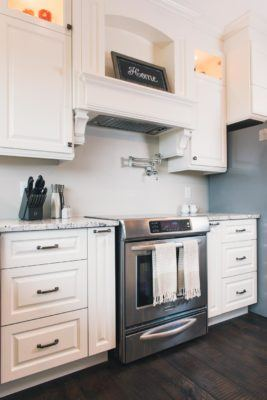 Range surrounded by white custom cabinets with pullouts and decorative range hood