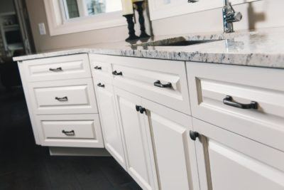 Lower kitchen cabinets shown in white with antique nickel hardware and quartz counterop
