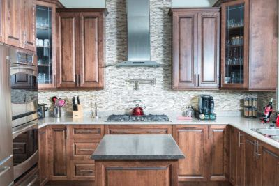 Stained birch kitchen with stainless steel range hood