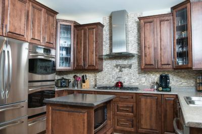 Overview of stained birch kitchen with stainless steel range hood