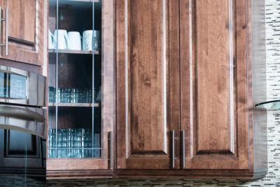 Detail of top birch cabinets in dark stain with pewter grill corner door