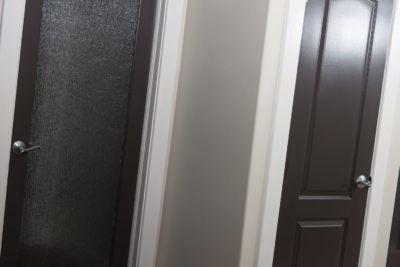 Rain glass door and 2 Panel arch doors in black shown with plain casing