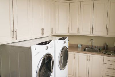 Large laundry room with off white cabinets