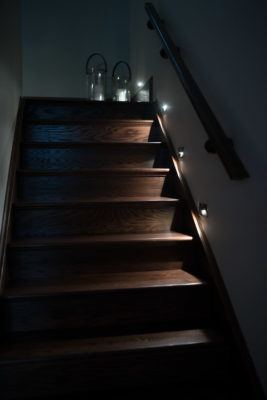 Oak Stairs in a dark stain shown with custom lighting