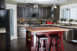 Overview of Solid birch cabinets with oak island stained red with solid birch butcher block top