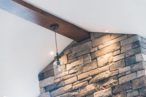 Custom pine beam on vaulted ceiling against a stone wall
