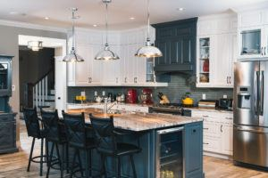 Overview of white custom kitchen cabinets with dark grey island and decorative hood