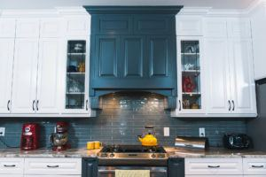 Dark grey decorative range hood surrounded by white cabinets with glass doors