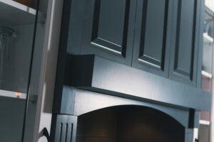 Detail of dark grey decorative range hood with shelf